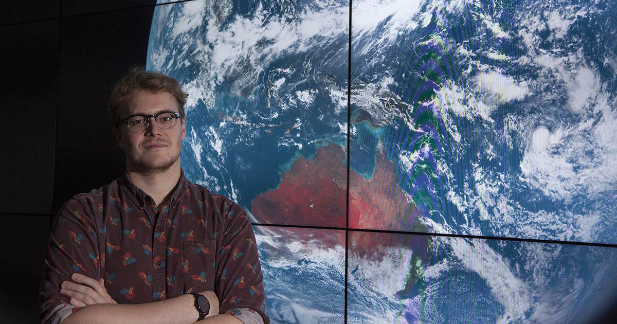 Jamon Van Den Hoek in front of a large screen satellite image