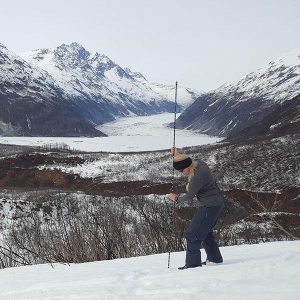 Researcher measuring snow depth in Alaska