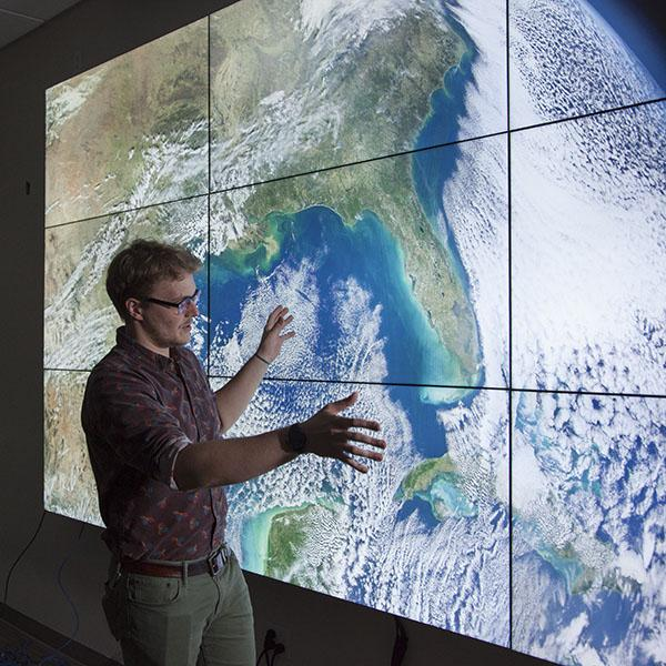 Jamon Van Den Hoek in front of a large screen satellite image